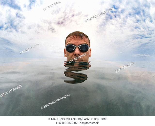 Young serious man in the sea, his head is on the smooth surface of the water, over him the cloudy sky, he wears goggles