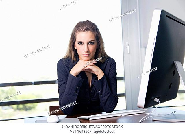 Portrait of a blonde woman at workplace with the computer