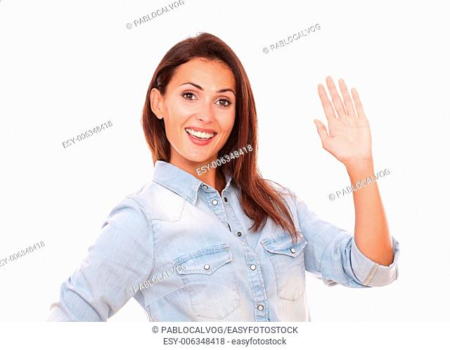 Portrait of adult hispanic female on blue blouse with greeting hand smiling at you on isolated studio