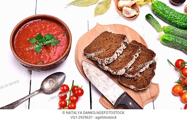 Gazpacho spanish cold soup in a round ceramic plate and bread, top view