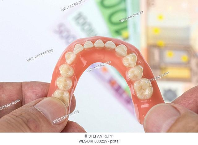 Hand holding dentures with Euro notes in background