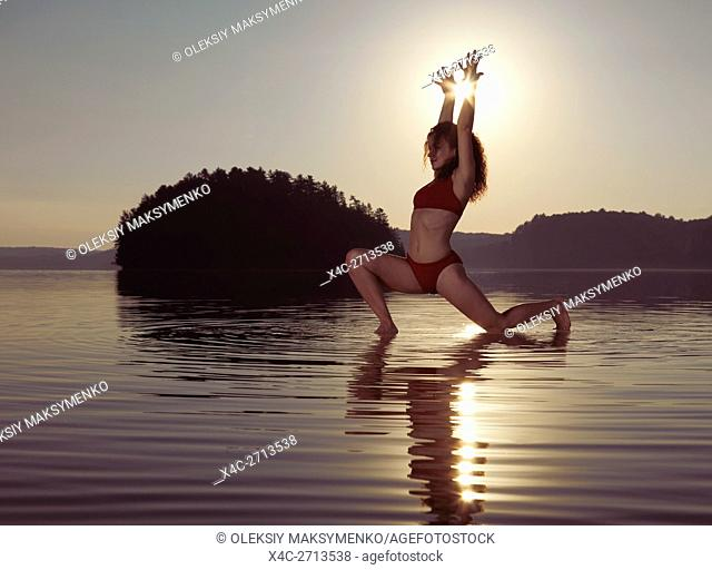 Young woman practicing Hatha yoga artistic variation of Low Lunge pose on a floating platform in water on the lake during misty sunrise in the morning
