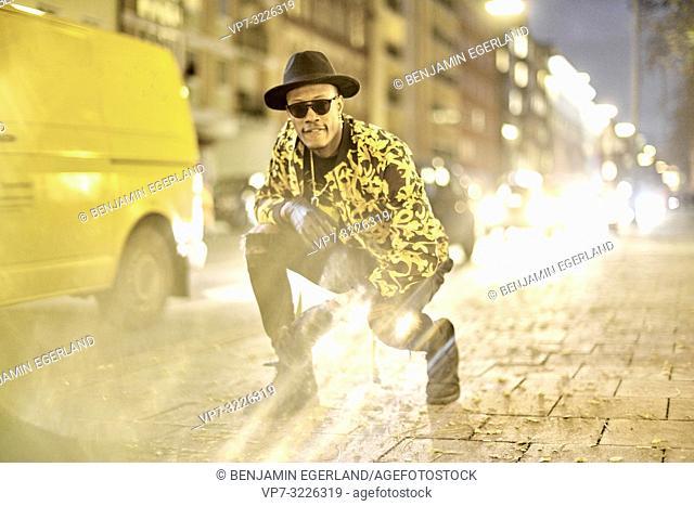 fancy man crouching on pavement, street, cool pose, stylish, outfit, night, traffic lights, in Munich, Germany