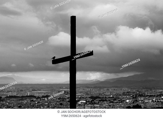 A wooden cross, pointing out a local church, is seen placed above the large outskirts in the south of Bogota, Colombia, 31 May 2010