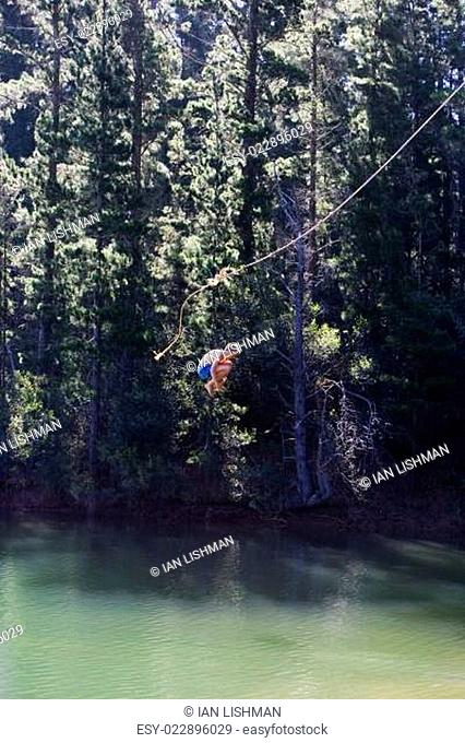 Boy (8-10), in swimming shorts, letting go of rope swing above lake, hugging knees, side view