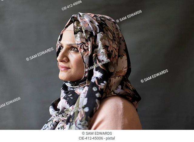 Serene, thoughtful woman wearing floral hijab, looking away