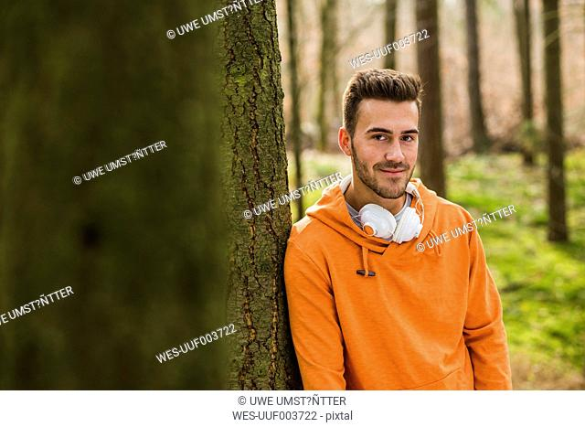 Smiling young man with headphones in forest