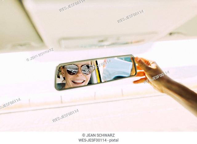 Reflection of happy young woman in rear-view mirror of a car