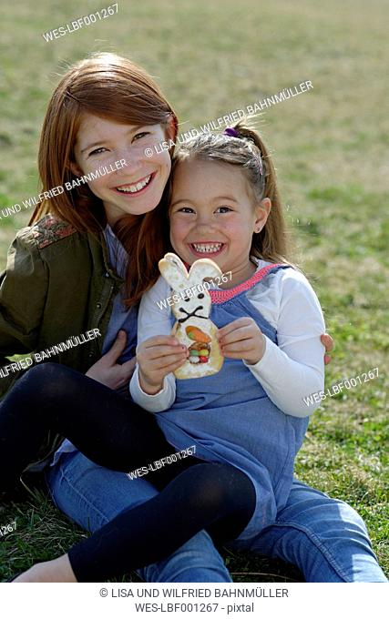 Two happy girls with pastry Easter bunny on meadow