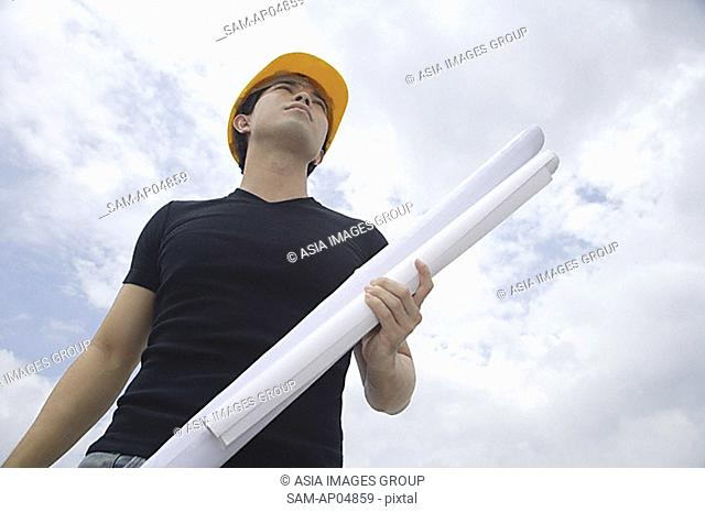 Young man wearing hardhat, carrying blueprints, low angle view