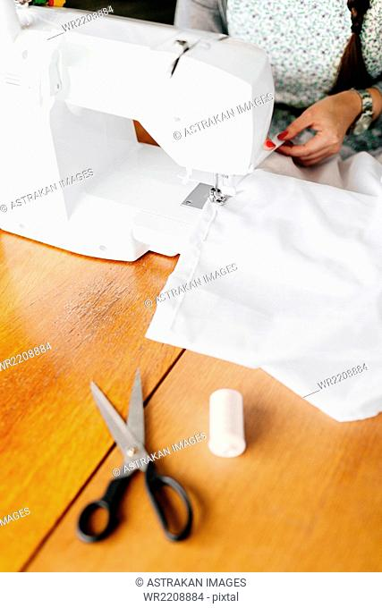 Midsection of professional using sewing machine at table in studio