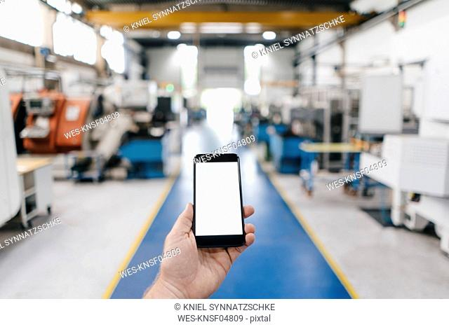 Hand holding smartphone with blank screen in a factory workshop