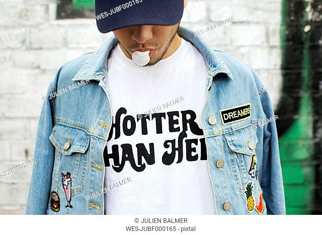 Young man with gum bubble wearing t-shirt with saying 'Hotter Than Hell'
