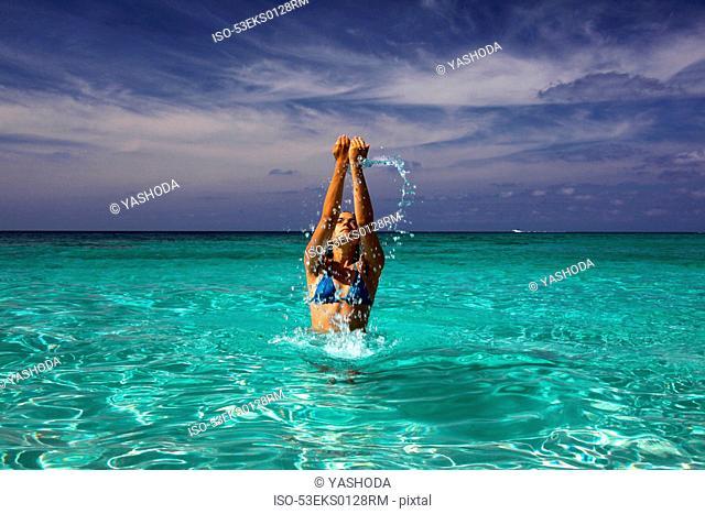 Woman splashing in tropical water