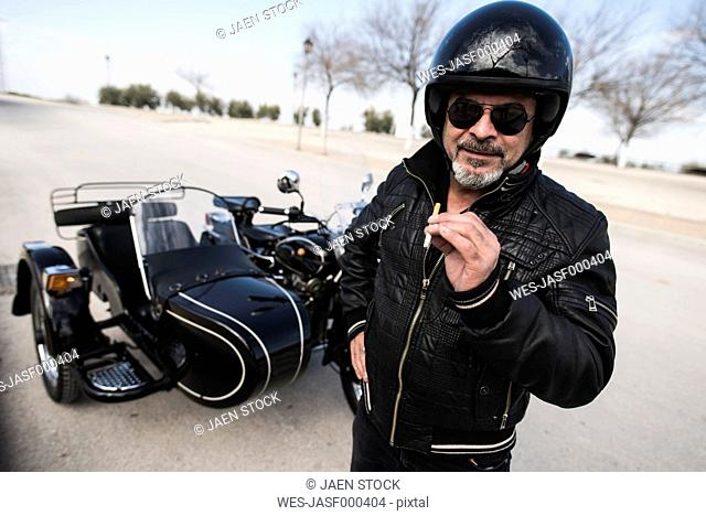Portrait of cool biker wearing helmet and sunglasses standing on a road in front of his sidecar motorcycle