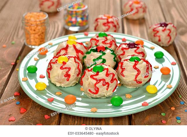 Funny cakes for Halloween on brown background