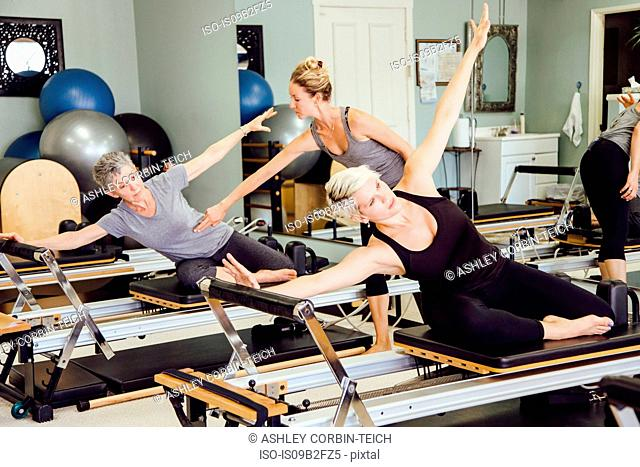 Women in gym using pilates reformer