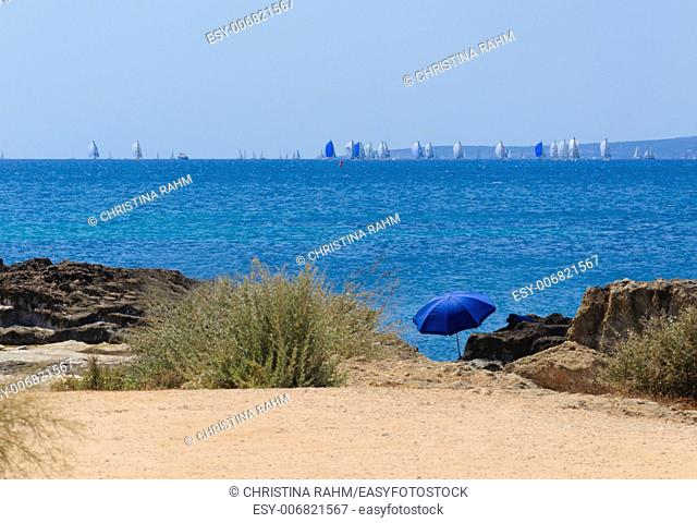 Blue parasol and the Copa del Rey regatta with blue sails in Palma Bay, Majorca, Spain
