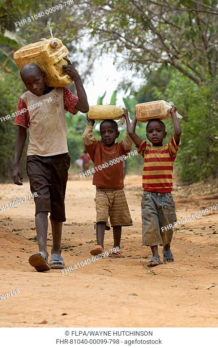 Children collecting and carrying home water from well, Rwanda