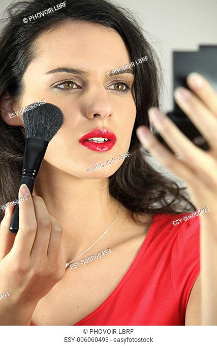 beautiful woman putting on some make up
