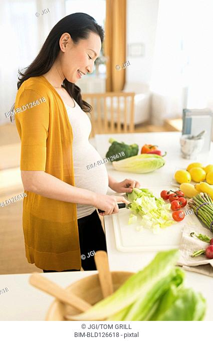 Pregnant Japanese woman slicing vegetables in kitchen