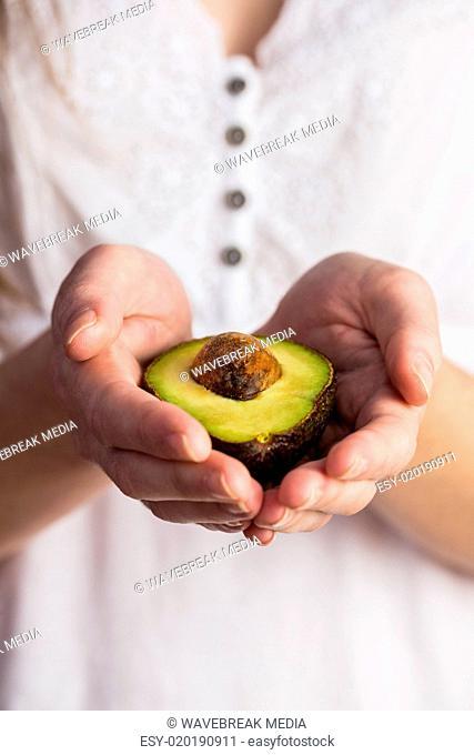 Woman showing fresh avocado