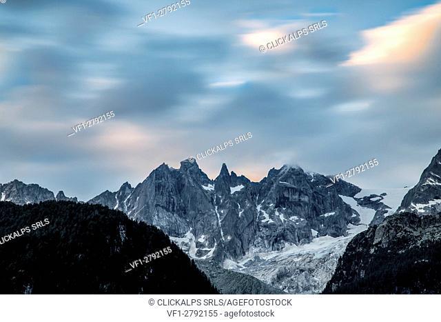 Clouds running fast over the granitic peaks of Sciore while dawn is coming. Soglio Val Bregaglia Canton of Graubunden Switzerland