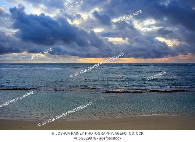 Dramatic sunrise and clouds over the Pacific Ocean off the coast of Oahu Hawaii on the North Shore