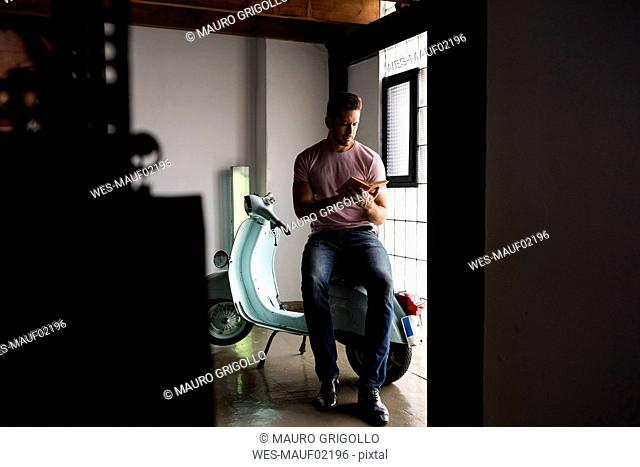 Man with motor scooter reading a book in a loft