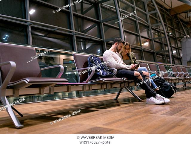 Couple using mobile phone in waiting area