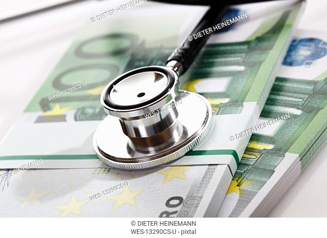 Stethoscope with Euro bank notes, close up