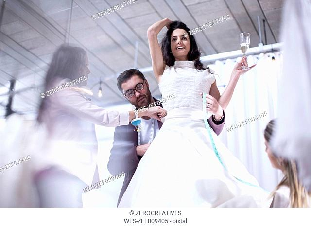 Woman holding glass of champagne trying on wedding dress