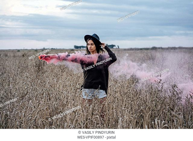 Portrait of young woman standing in a corn field with smoke torch