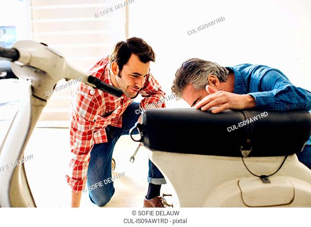 Mature man and adult son checking moped in garage