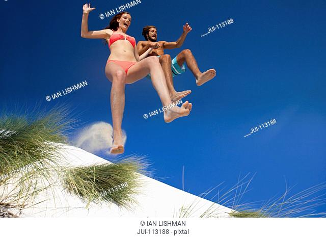 Couple jumping for joy over sand dune beach hill