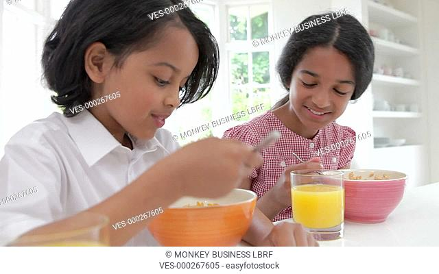 Two children sitting at kitchen counter eating bowls of cereal and talking.Shot on Canon 5d Mk2 with a frame rate of 25fps