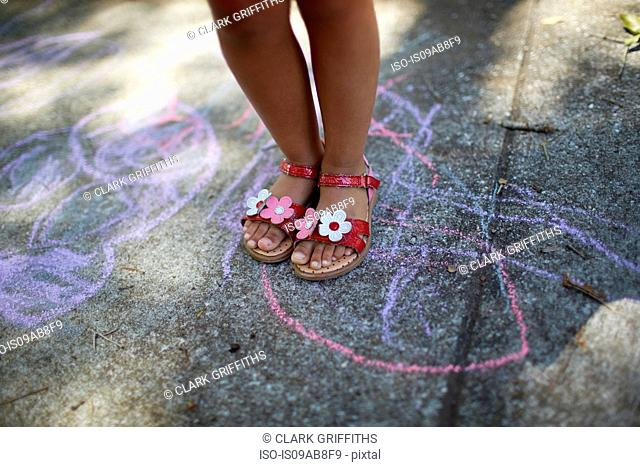 Girl's legs standing on chalk drawing