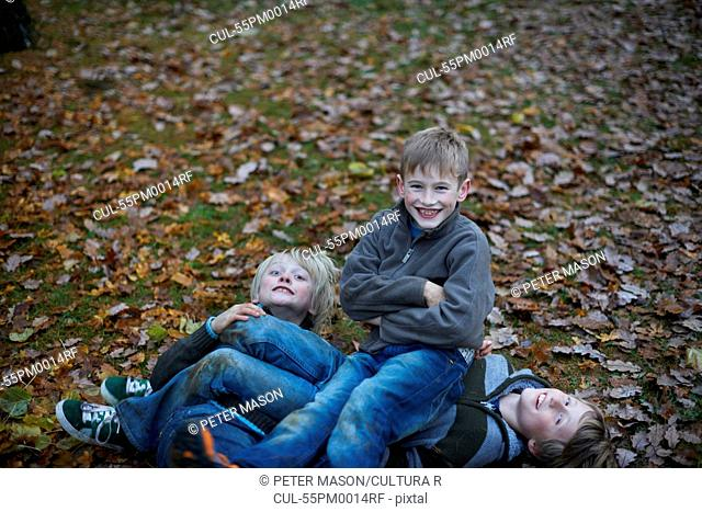 Boys play fighting on forest floor