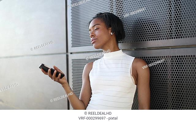Afro American using smartphone outdoors