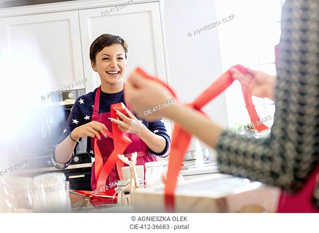 Smiling female caterers wrapping baked goods in boxes with red ribbon in kitchen