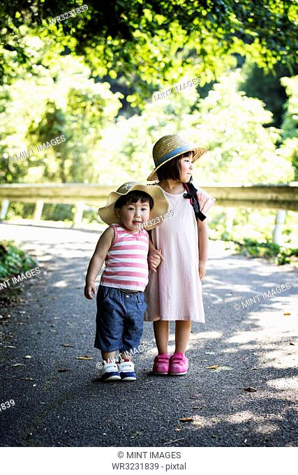 Two Japanese girls wearing sun hats standing on path, holding hands