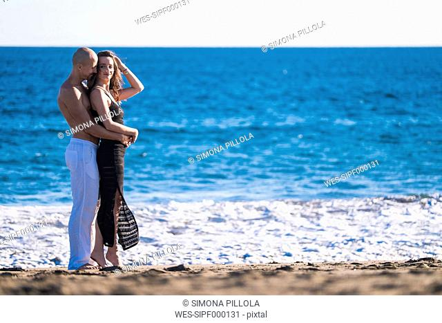 Spain, Tenerife, happy couple standing at seafront of the beach