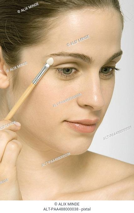 Woman putting on eye shadow, close-up