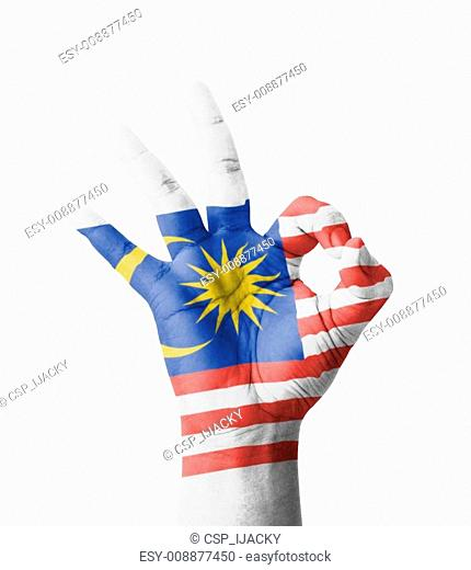 Hand making Ok sign, Malaysia flag painted as symbol of best quality, positivity and success - isolated on white background