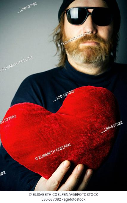 Man holding red heart pillow