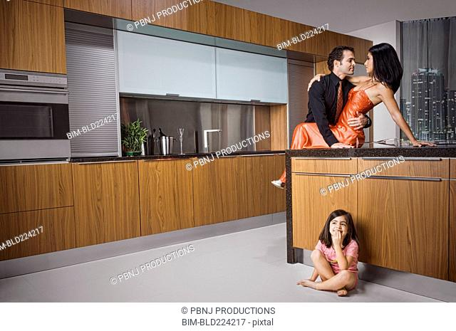 Caucasian girl eavesdropping on parents in kitchen