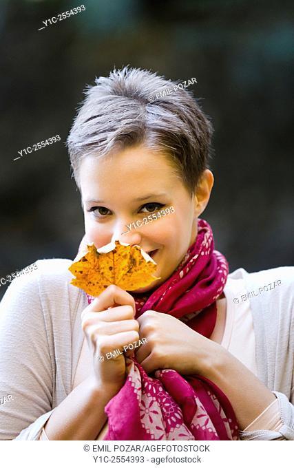 Shy teenager girl behind Autumn leaf