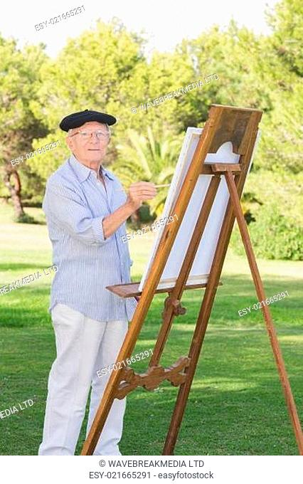 76fc29c86564d Portrait of old man wearing beret painting a canvas in the park