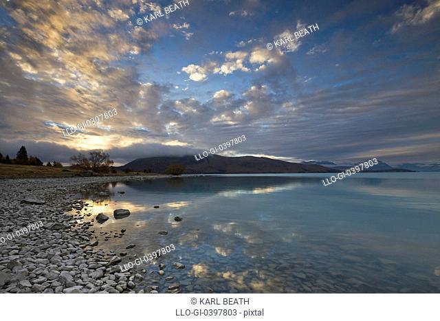 The sun sets over the blue waters of Lake Tekapo, Otago, South Island, New Zealand
