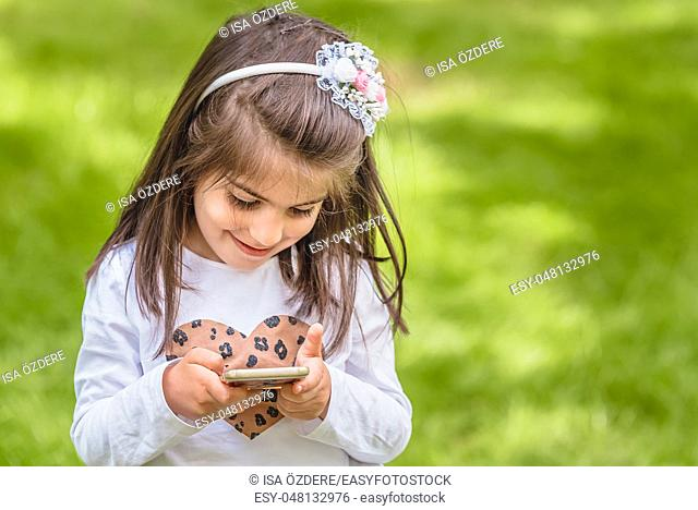 Adorable four years old cute little girl in casual clothes holds and texts mobile phone while smiling at outdoor in park